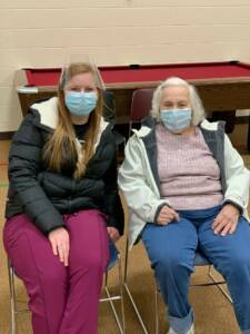 A young woman wearing a face shield and mask sits next to an elderly woman with grey hair who is also wearing a mask