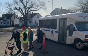 A LifeCircles bus is parked behind a group of people walking.